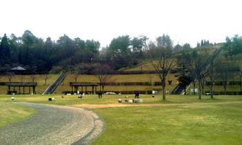 【写真】信楽陶芸の森。太陽の広場とダイエット階段を東側から望む。犬と遊ぶ人たち。曇り空。