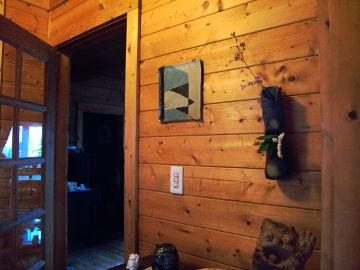 【写真】陶工房 滋風の玄関右手の壁。手前上に、豆桜(キンキマメザクラ?)と馬酔木を生けた Sigeru の掛花。手前下に、Sigeru の森の精。奥上に Sigeru の絵皿。奥下に、Sigeru の香炉と風花の招き猫カード立て。