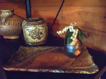 【写真】陶工房 滋風の陳列棚下段。Sigeru の長方皿の上に、馬酔木を生けた Sigeru の一輪挿し。奥に Sigeru の蓋物と花器。
