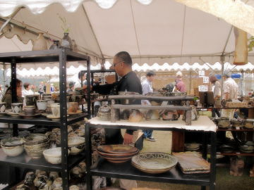 【写真】第 7 回しがらき作家市、陶工房 滋風のブースの様子。右手奥から。Sigeru のビア・マグ(大)を手に取る、サングラスを着用したスキンヘッドの男性。画面手前に、Sigeru の花器, マグ, 大皿, コーヒー・カップ & ソーサー, 丼ぶり, 飯碗など。[撮影:Sigeru]