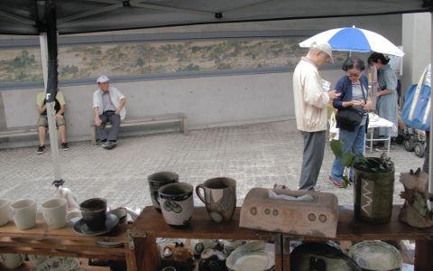 【写真】北山クラフト ガーデン、ブース内より。手前(ブース奥側)右手に Sigeru の森の精, 花生, ティッシュ・ボックス, ビア・マグなど。左手に風花のゆのみなど。奥(ブース前)の左手のベンチに座る男性。右手に年配の男女。壁には「清明上河圖」の陶板壁画。