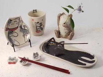 【写真】左上から時計回りに、風花の猫柄小皿, 猫柄フリー・カップ, 猫一輪挿し, 猫香立て長皿, 猫柄箸置き, 猫ブローチ。箸置きには赤い漆塗りの箸。一輪挿しの花は額紫陽花。