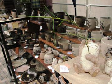 【写真】笹を持つ風花の招き猫一輪挿し。北山クラフト ガーデン、陶工房 滋風のブースにて。手前には、風花の猫マグネット。背後、右側に、風花の猫雑貨(招き猫カード・スタンドなど)と猫柄食器(猫柄マグや猫柄フリー・カップなど)、左側に、Sigeru の食器(高坏湯呑みやマグ, 湯呑み, コーヒー・カップ & ソーサー, 平鉢など) と雑貨。その向こう側に、隣のブースの羊毛のマフラー。