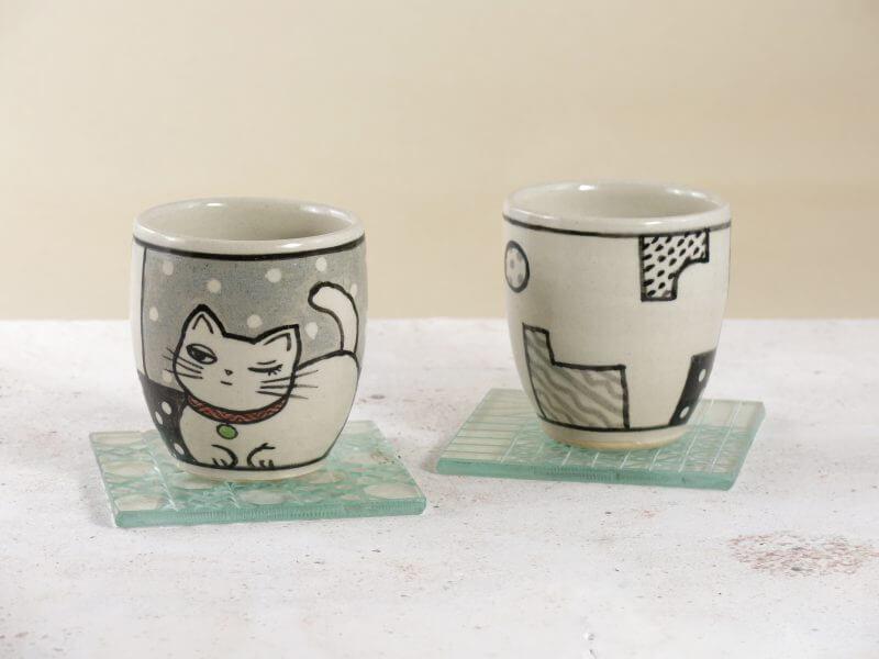 猫の絵が描かれた、湯呑み(フリー・カップ)が2客。白い生地の色には、釉薬の控えめな光沢感がある。左は正面の柄が見えている。黒い呉須絵で描かれた、片目をつぶってウィンクをしている、女性的な顔の、香箱座りの白猫。赤い首輪と緑色の鈴。背景は上が灰色で下が黒の大きな格子の中に小さな白いドット柄。右は裏の柄が見えている。波線や水玉模様が描かれた幾何学的な図形が、黒とグレーで白地に描かれている。ガラスのコースターに乗っている。